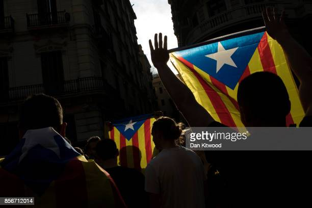 Protesters hold up flags as they gather outside the 'General Direction of the National Police of Spain' offices as Catalonian police officers...