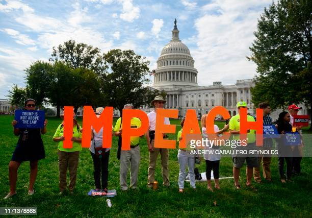 "Protesters hold up letters reading ""impeach"" in front of the US Capitol building during the ""People's Rally for Impeachment"" on Capitol Hill in..."