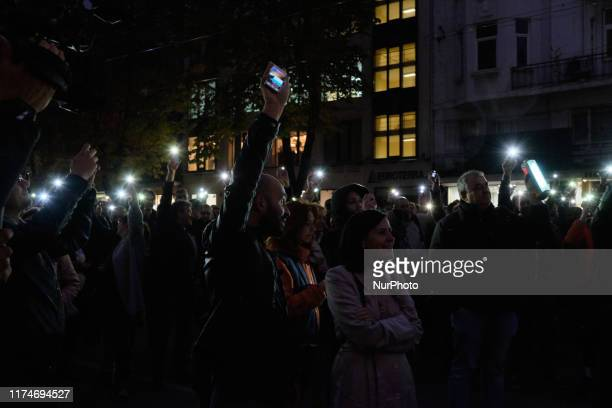 Protesters hold up lights during the march Lets Turn On the Light in the Darkness in the Bulgarian capital Sofia on Tuesday, October 8 to voice their...