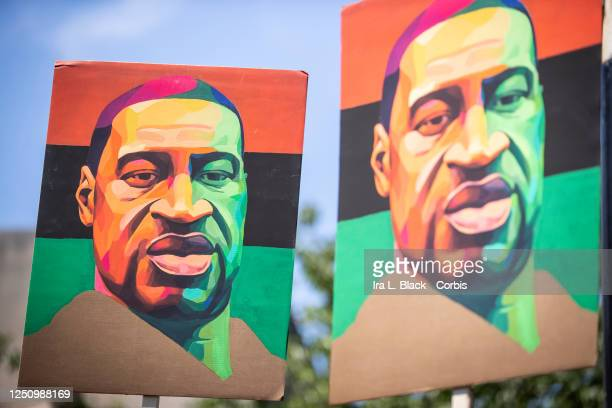 Protesters hold up painted portraits of George Floyd with the PanAfrican colors of Red Black and Green as speakers talk to the thousands of...