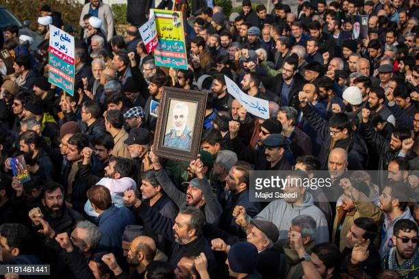 Protesters hold up photographs as people demonstrate after the US airstrike in Iraq that killed Iranian Revolutionary Guard Gen Qasem Soleimani on...