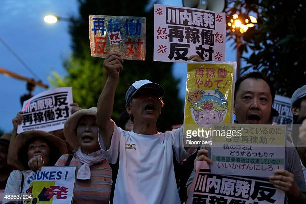 Protesters hold up placards and shout slogans as they take part in a rally against the restarting of the No 1 reactor at Kyushu Electric Power Co's...