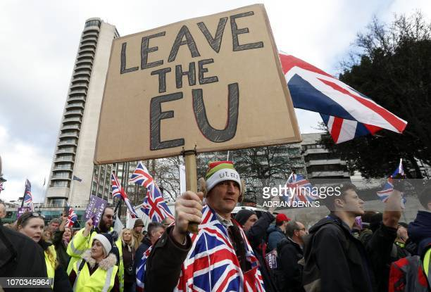 TOPSHOT Protesters hold up placards and Union flags as they attend a proBrexit demonstration promoted by UKIP in central London on December 9 as the...