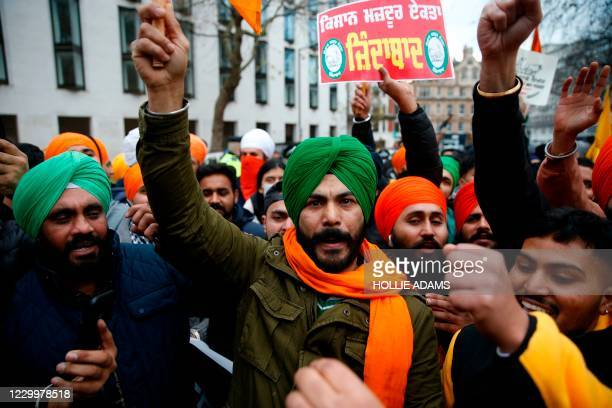 Protesters hold up placards as the gather outside the Indian High Commission in central London on December 6 as global protests against the Indian...