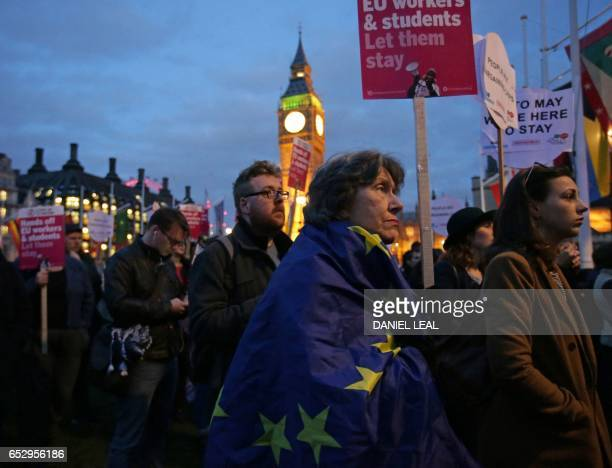 Protesters hold up placards as they take part in a protest in support of an amendment to guarantee legal status of EU citizens outside the Houses of...