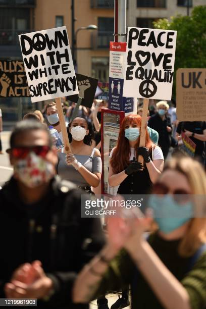 Protesters hold up placards at a gathering in support of the Black Lives Matter and Black Voices Matter movements in central Leeds in northern...