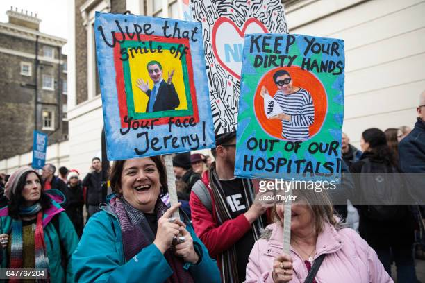 Protesters hold up placards during a demonstration in support of the NHS in Tavistock Square on March 4 2017 in London England Thousands march from...