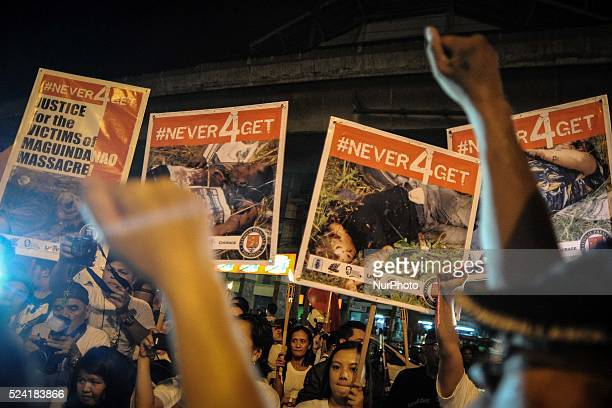 Protesters hold up placards with pictures of the bodies from the 2009 massacre in Maguindanao during a demonstration outside the presidential palace...