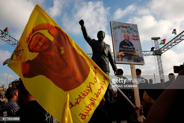 TOPSHOT Protesters hold up portraits of Palestinian leader and prominent prisoner Marwan Barghouti in front of a statue of Nelson Mandela in the West...