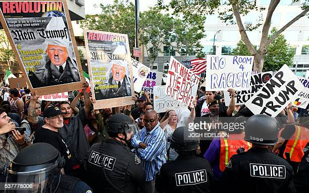Protesters hold up signs against a police skirmish line near where Republican presidential candidate Donald Trump holds a rally in San Jose...