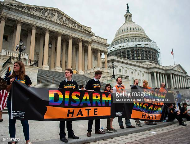 Protesters hold up signs and flags to show solidarity with House Democrats after they staged a sit in over guncontrol laws on Capitol Hill in...