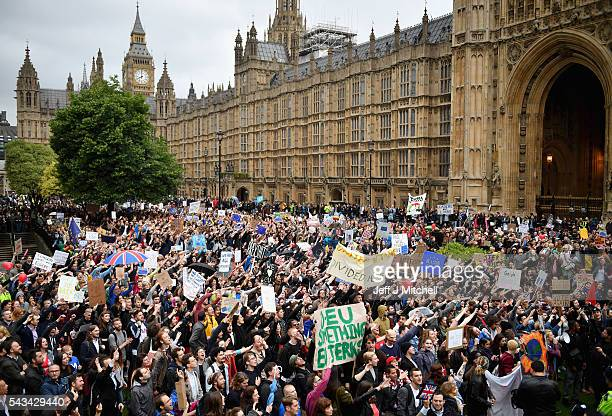 Protesters hold up signs and wave in unison as they demonstrate against the EU referendum result outside the Houses of Parliament on June 28 2016 in...