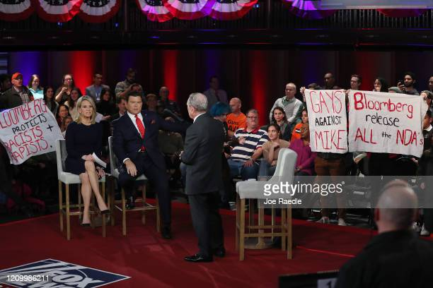Protesters hold up signs as Democratic presidential candidate former New York City mayor Mike Bloomberg participates in a FOX News Town Hall with...