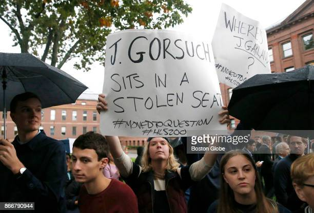 Protesters hold up signs as Supreme Court Justice Neil Gorsuch walks past them as part of a procession to mark Harvard Law School's bicentennial in...