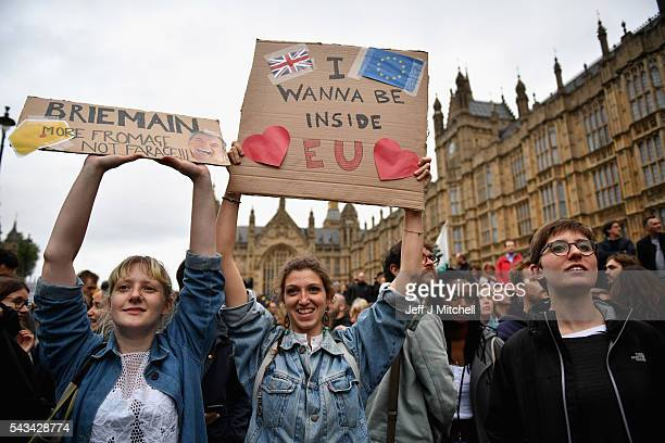 Protesters hold up signs as they demonstrate against the EU referendum result outside the Houses of Parliament on June 28 2016 in London England Up...