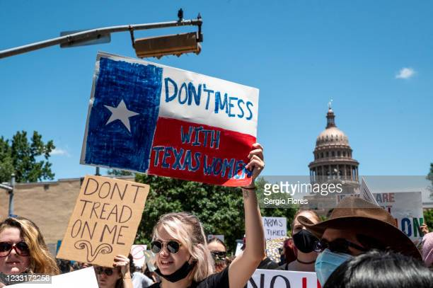 Protesters hold up signs as they march down Congress Ave at a protest outside the Texas state capitol on May 29, 2021 in Austin, Texas. Thousands of...