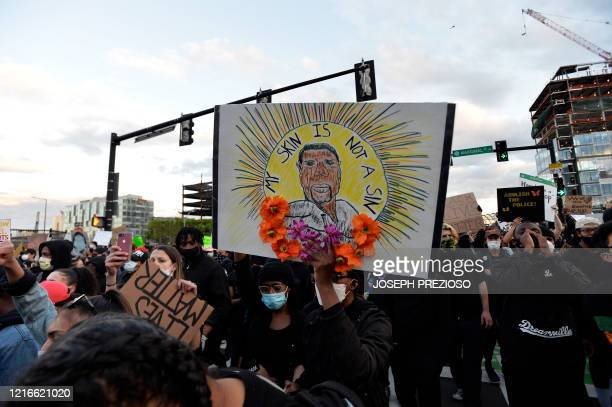Protesters hold up signs as they march during a demonstration over the death of George Floyd an unarmed black man who died in Minneapolis Police...