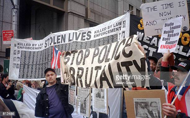 Protesters hold up signs as they march from Brooklyn to Manhattan April 15 1999 in New York City during a protest against the alleged police...