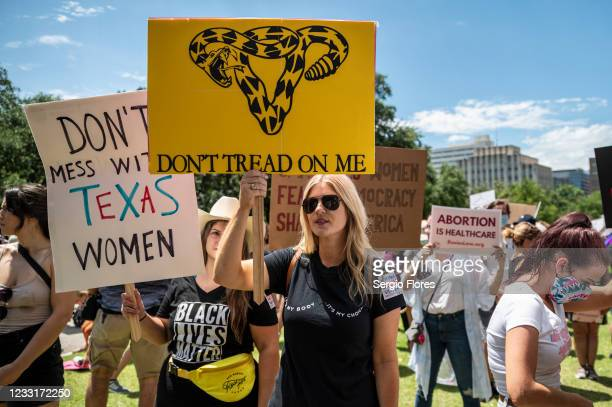 Protesters hold up signs at a protest outside the Texas state capitol on May 29, 2021 in Austin, Texas. Thousands of protesters came out in response...