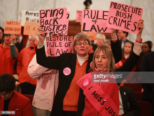 Protesters hold up signs during Attorney General nominee Eric Holder's confirmation hearing in front of the Senate Judiciary Committee on Capitol...
