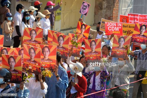 Protesters hold up signs featuring Aung San Suu Kyi during a demonstration against the military coup in Naypyidaw on February 22, 2021.