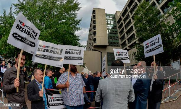 Protesters hold up signs reading 'End Terrorism' before the proclamation of sentence in the trial against Beate Zschaepe the only surviving member of...