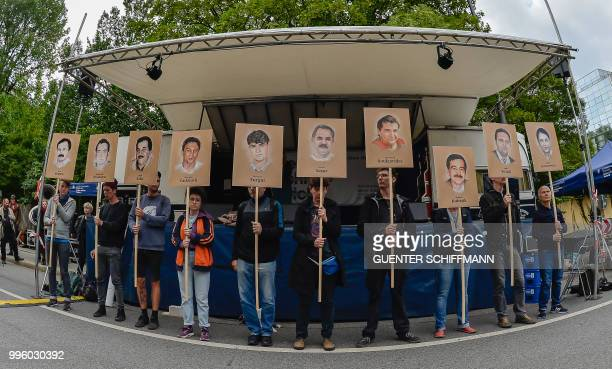 TOPSHOT Protesters hold up signs with pictures of the victims of neoNazi cell National Socialist Underground before the proclamation of sentence in...
