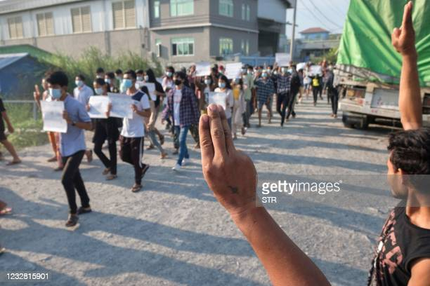Protesters hold up the three finger salute during a demonstration against the military coup in Mandalay on May 11, 2021.