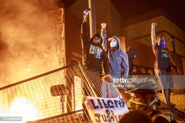 TOPSHOT Protesters hold up their fists as flames rise behind them in front of the Third Police Precinct on May 28 2020 in Minneapolis Minnesota...