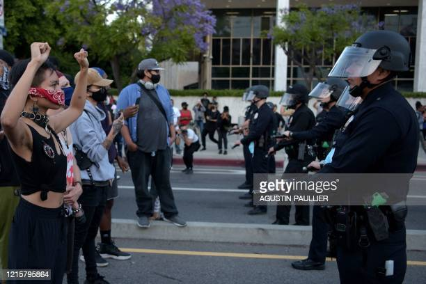 TOPSHOT Protesters hold up their fists in front of a row of police officers as protesters gather in downtown Los Angeles on May 27 2020 to...