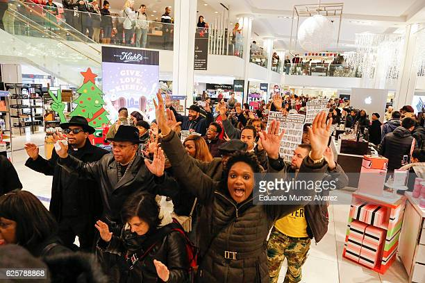Protesters hold up their hands as they demonstrate against racial injustice and police brutality during Black Friday events at Macy's retail store on...