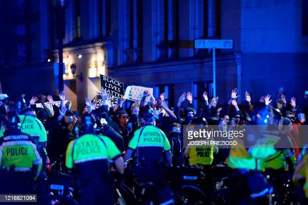 Protesters hold up their hands as they face police after a demonstration over the death of George Floyd an unarmed black man who died in Minneapolis...