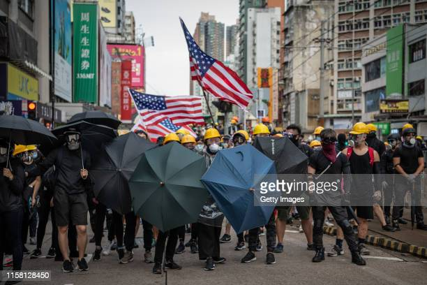 Protesters hold up umbrellas and American flags in the face of advancing riot police in the district of Yuen Long on July 27 2019 in Hong Kong China...
