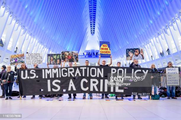 Protesters holding a banner at the silent protest. Members of the activist group Rise And Resist gathered a silent protest inside The Oculus at the...