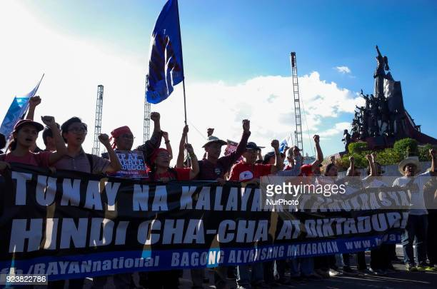 Protesters holding a banner raise clenched fists during a protest ahead of the 32nd anniversary of the EDSA People Power Revolution at the People...