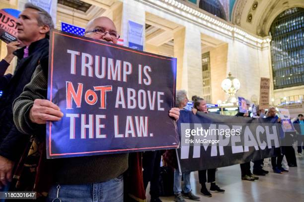 Protesters holding a banner reading IMPEACH On the heels of the corrected testimony of US Ambassador to the EU Gordon Sondland admitting he delivered...