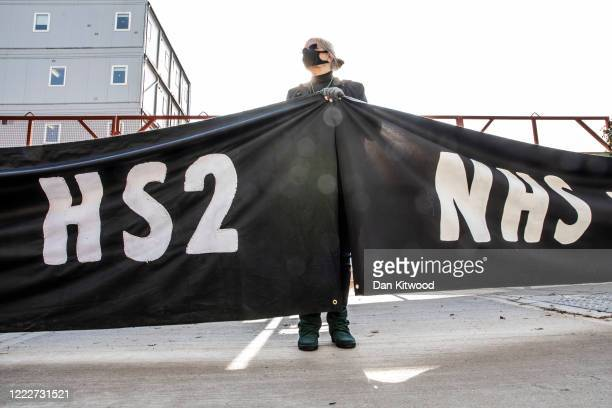 Protesters holding a banner that reads 'NHS not HS2' stand by a gate to the HS2 site near Euston Station on May 04 2020 in London England A campaign...