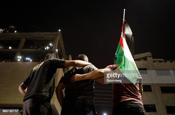 Protesters holding a Jordanian national flag look on during a demonstration against a draft income tax law near the prime minister's office in Amman...