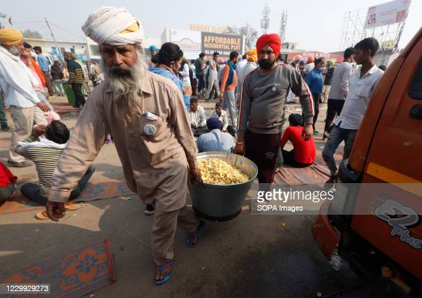 Protesters holding a saucepan with meals during the demonstration. As part of the Delhi Chalo march against the Centre's new farm laws 000 farmers...