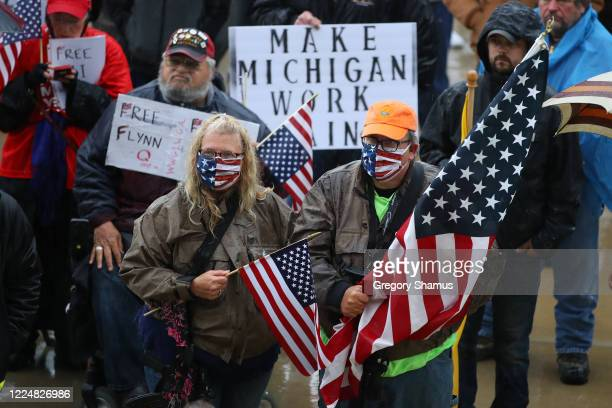 Protesters holding American flags gather at the Michigan Capitol Building on May 14 2020 in Lansing Michigan Protesters are angry at Michigan...