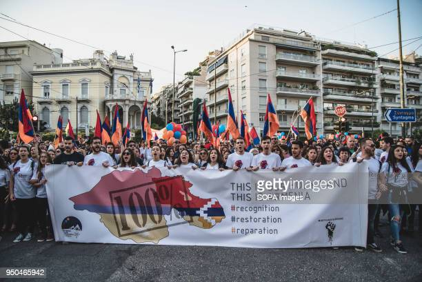Protesters holding flags and banners shouting slogans while marching towards the Turkish Embassy during a demonstration to mark the 103rd anniversary...