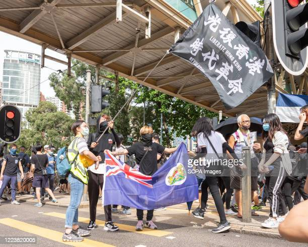 Protesters holding flags demanding Hong Kong independence outside Victoria Park Thousands took to the streets of Hong Kong on the 23rd anniversary of...