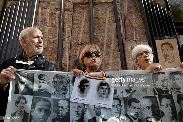 Protesters holding pictures of alledged victims of Franco's regime shout slogans during a hearing with Argentinian judge Maria Servini de Cubria...