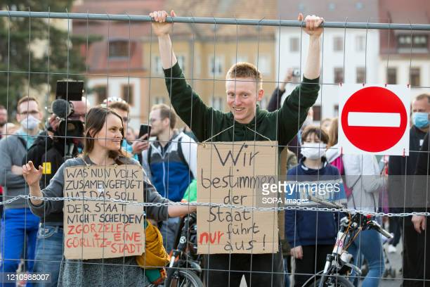 Protesters holding placard stand behind the fence on the German side of The Zgorzelec-Gorlitz Old Town Bridge during the demonstration. Hundreds of...
