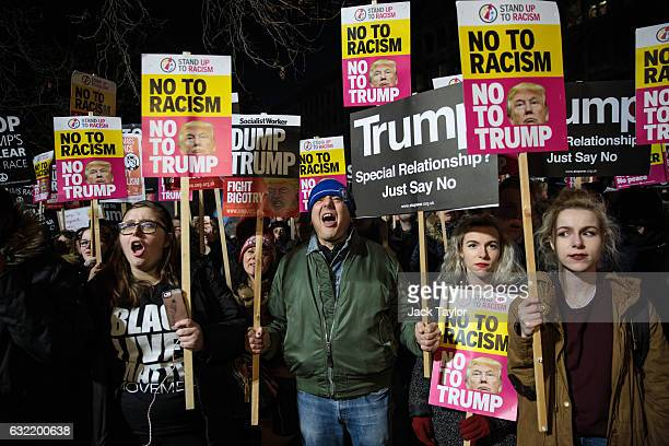 Protesters holding placards attend a demonstration against US President Donald J Trump outside the United States Embassy in London on January 20 2017...