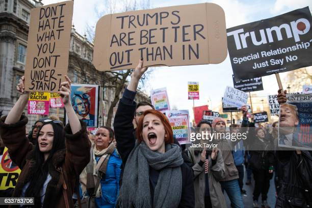 Protesters holding placards cheer as they take part in a demonstration against US President Donald Trump on Whitehall on February 4 2017 in London...