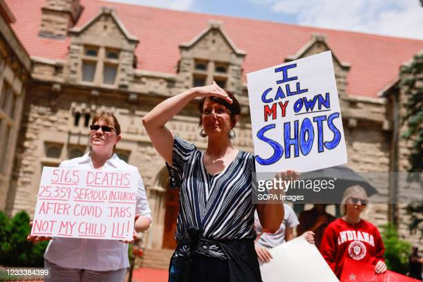 Protesters holding placards gather at Indiana University's Sample Gates during the demonstration. Anti-vaxxers and anti-maskers gathered at Indiana...