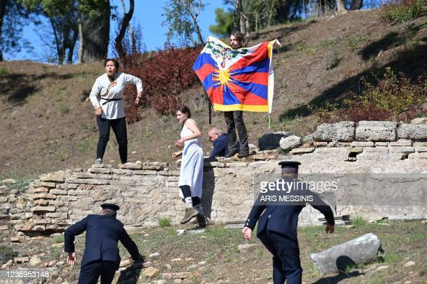 Protesters holding the Tibetan flag crash the flame lighting ceremony for the Beijing 2022 Winter Olympics at the Ancient Olympia archeological site,...
