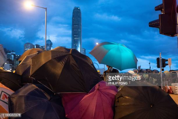 Protesters holding umbrellas set up barricades at Lung Wo road outside the Legislative Council in Hong Kong before the flag raising ceremony to mark...