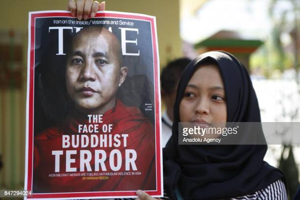 A protesters holds a banner reading 'The Face of Buddhist Terror with the image of Myanmar Buddhist Monk Wirathu' during a demonstration in support...